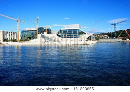 OSLO NORWAY AUGUST 17 2016: Tourist on the Oslo Opera House which is home of Norwegian National Opera and Ballet and National Opera Theatre in Oslo Norway on August 172016.