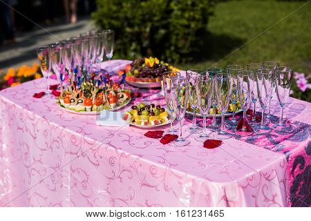 empty glasses stand on a festive table with food preparation for the wedding feast fruit on the wedding table canapés