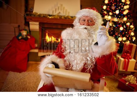 Portrait of happy Santa Claus sitting at his room at home near Christmas tree with wish list