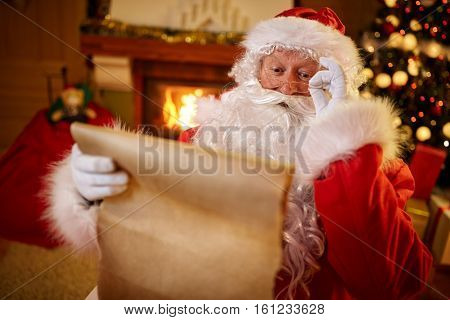 happy Santa Claus sitting at his room at home near Christmas tree and reading Christmas letter or wish list