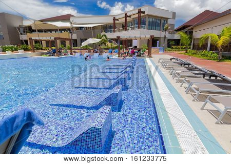 Cayo Coco island, Pullman hotel, Cuba, June 28, 2016, beautiful amazing fragment of view of luxury blue ceramic, mosaic tiles swimming pool with sun beds and people relaxing in background on sunny gorgeous day