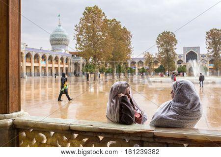 Shiraz, Iran - December 24, 2015: Two unidentified iranian woman talk to each other  in famous Shah-e-Cheragh Shrine and mausoleum (Mirror mosque) in Shiraz, Iran