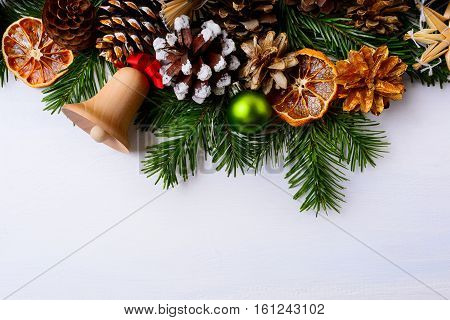 Christmas greeting with jingle bell dried oranges and green ornament . Christmas background with handmade decorations. Christmas decoration with fir branches and pine cones. Copy space