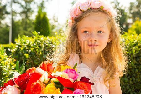 Adorable little child girl with bouquet of flowers on happy birthday. Summer green nature background. Use it for baby parenting or love concept