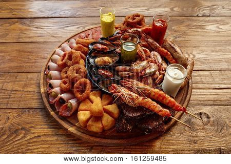 Seafood platter. Mediterranean cuisine restaurant food, fried calamari rings, king prawns, mussels, oysters, shellfish delicacy on wood table background. Catering, banquet table