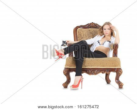 Fashion blonde in red shoes sitting in throne