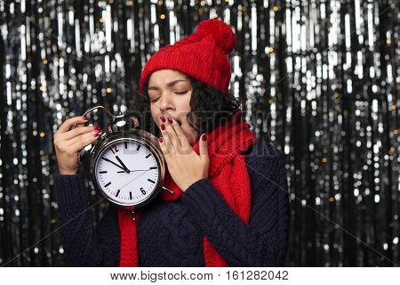 New Year eve concept. Boring woman in winter hat and scarf holding with big alarm clock counting to midnight yawning