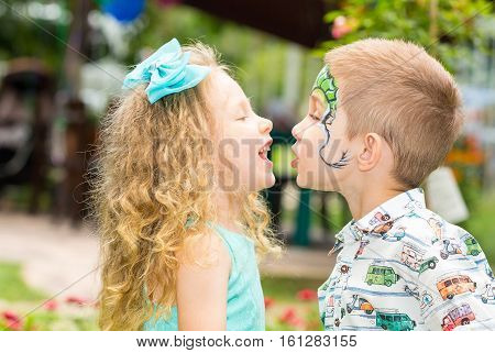 The boy and girl child with aqua make-up on happy birthday. Celebration concept and childhood love
