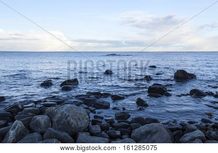 Baltic Sea, coast and shore. Stones and rocks in the evening. Clouds in the background.