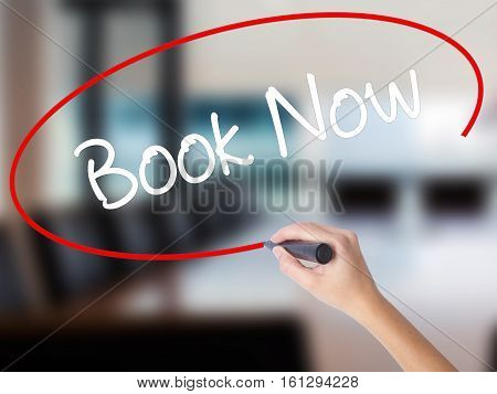 Woman Hand Writing Book Now With A Marker Over Transparent Board