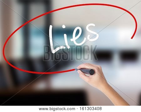Woman Hand Writing Lies With A Marker Over Transparent Board