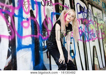 jovem de pé na parede grafite