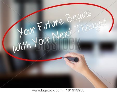 Woman Hand Writing Your Future Begins With Your Next Thought With A Marker Over Transparent Board.