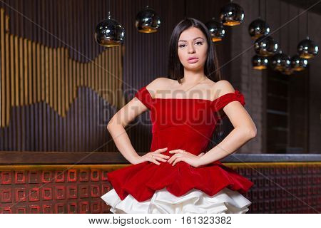 Elegant young woman in evening dress posing in interior. Fashion style portrait of a beautiful girl in interior