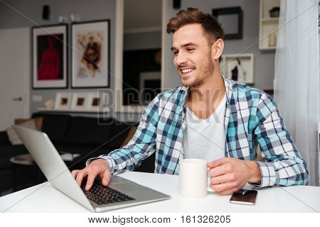 Image of laughing young man dressed in shirt in a cage print sitting in home and using laptop computer. Looking at laptop while drinking tea.