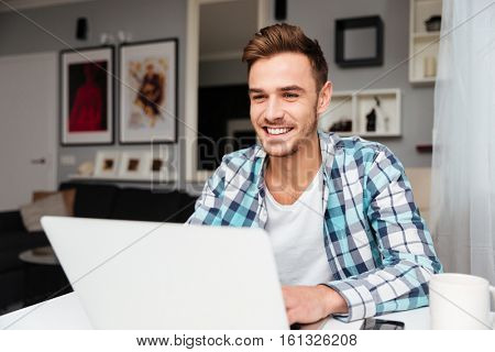 Picture of happy bristle man dressed in shirt in a cage print sitting in home and using laptop computer. Looking at laptop computer.