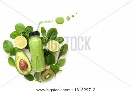 Bottled detox drink surrounded by green foods including spinach and kiwi