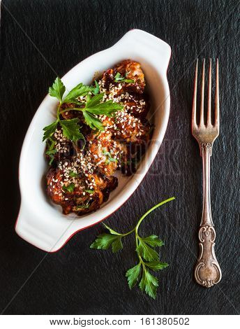Glazed pork with homemade sauce made from onions garlic tomatoes mustard vinegar honey soy sauce and sesame seeds. Black stone background baking dish fresh parsley.