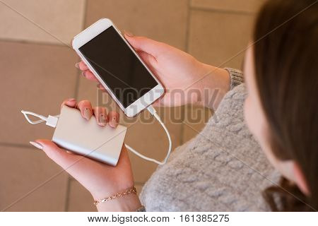 Girl Hold In Hands Smart Phone And Power Bank. Charge Smart Phone From Power Bank.