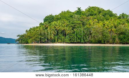 Bamboo Huts under Palm Trees of an Homestay on Gam Island, West Papuan, Raja Ampat. Indonesia.