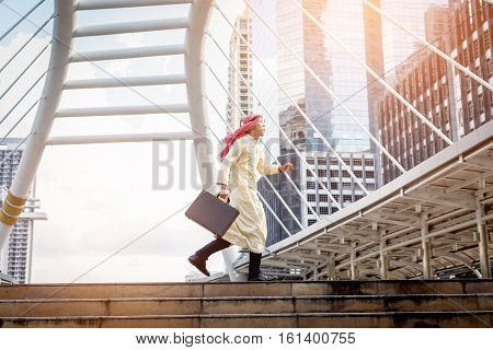 Young Muslim Business Man  Holding Bag And Running Rapidly To Airport. In Rush Hour At Stairway In U