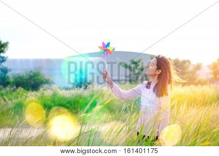 Silhouette Of Beautiful Girl Holding Wind Toy Or Wind Turbine Or Pinwheel And Wool Hat At Meadow On