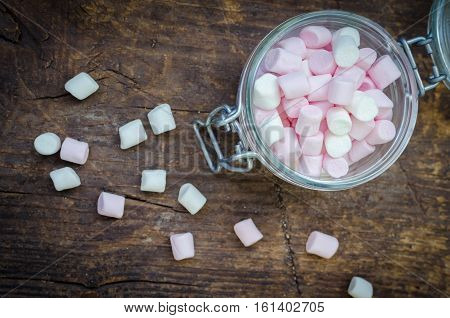 Pink and white mini marshmallows in a jar on an old rustic wooden table with space for text. Mini white and pink puffy marshmallows. Marshmallow concept. Copy space. Top view.
