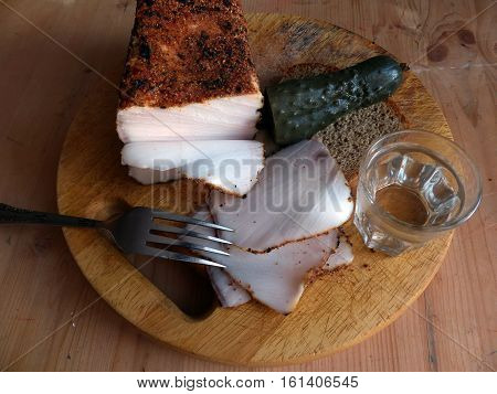 Homemade lard with condiments. Fresh bread, a glass of vodka, pickled cucumber. Natural food, appetizer. Closeup. Traditional Dishes of Russian Cuisine