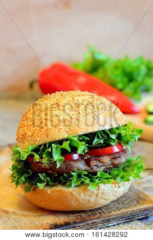 Sandwich with a fried bean burger, lettuce, red bell pepper and cucumber. Wholesome sandwich on a wooden board, fresh vegetables. Simple vegan sandwich idea. Vintage style. Closeup