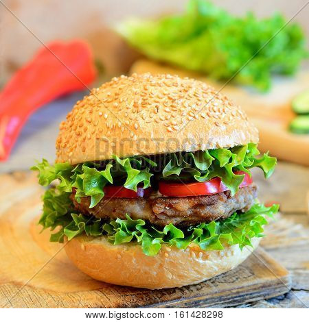 Sandwich with a bean burger, fresh lettuce, red bell pepper and cucumber. Healthy sandwich on a wooden board, fresh vegetables. Simple vegetarian sandwich idea. Vintage style. Closeup