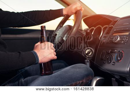 Young man drinking beer while driving car. Transportation and vehicle safety.