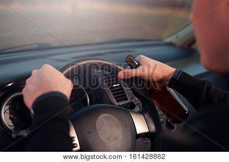Cropped shot of male driver holding steering wheel and drinking beer. Driving under influence of alcohol.