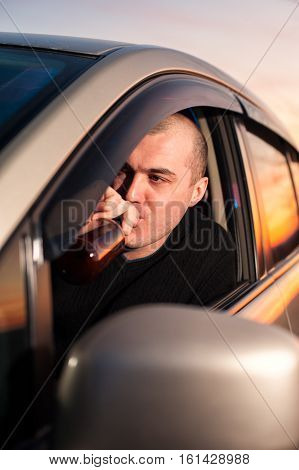 Young Man Drinking Beer While Driving Car