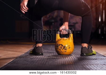 Cropped shot of young woman exercising with kettlebell. Sporty girl doing workout in gym.