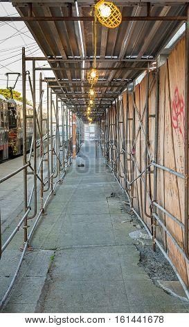 Detour under scaffolding of construction building next to railway