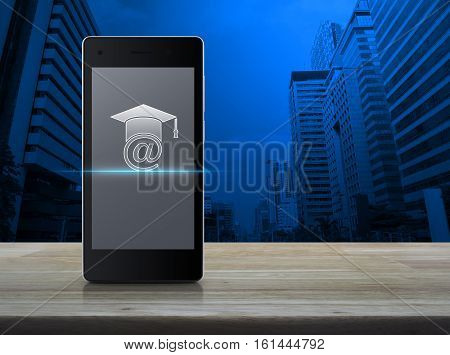 E-learning icon on modern smart phone screen on wooden table in front of city tower background Study online concept
