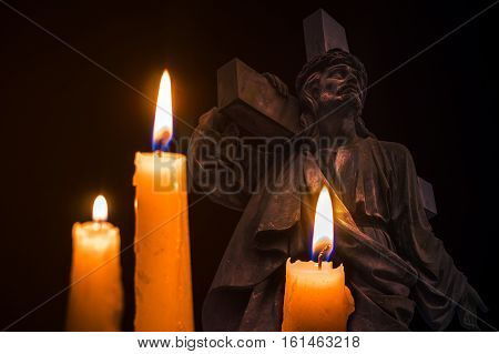 three burning candles on the background of Jesus with the cross on his shoulder