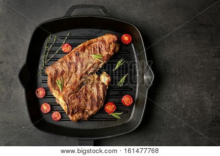 Composition of tasty steak, cherry tomatoes and herbs on pan