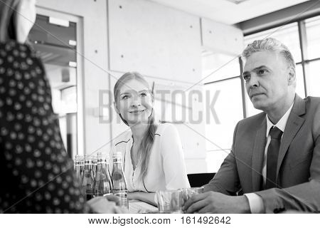 Smiling young businesswoman with colleagues in board room