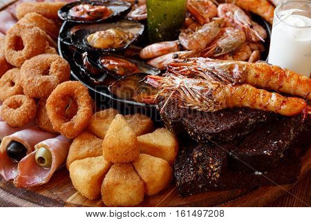 Seafood platter. Mediterranean cuisine restaurant food closeup, fried calamari rings, king prawns, mussels, oysters, shellfish delicacy on wood table background. Catering, banquet table
