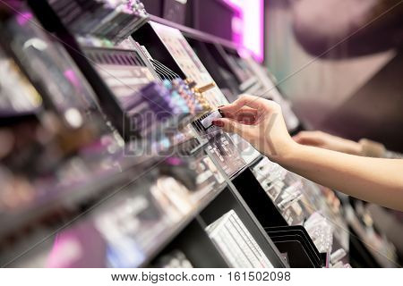 Woman Choosing color cosmetics in the store cosmetics, close up hand picks mascara tester