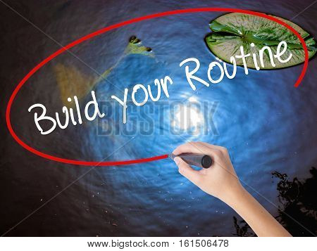 Woman Hand Writing Build Your Routine With Marker Over Transparent Board