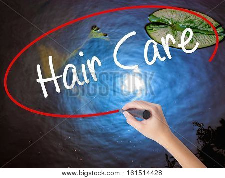 Woman Hand Writing  Hair Care With Marker Over Transparent Board