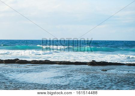 sea or ocean foaming waves rolled on coast with blue sky horizon as natural background