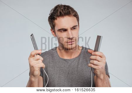 Portrait of a focused young man charging mobile phone over white background