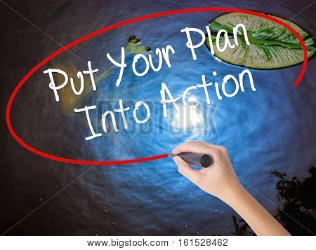 Woman Hand Writing Put Your Plan Into Action With Marker Over Transparent Board