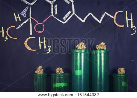THC formula handwritten on black board with cannabis buds - medical marijuana concept background