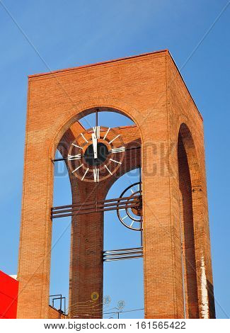 Modern electronic clock on the tower. 12:00.