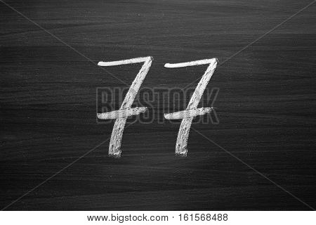 number seventy seven enumeration written with a chalk on the blackboard