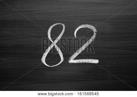 number eighty two enumeration written with a chalk on the blackboard